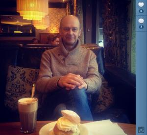 Hannes sitter i soffan på Centralkonditoriet. På bordet kaffe och latte