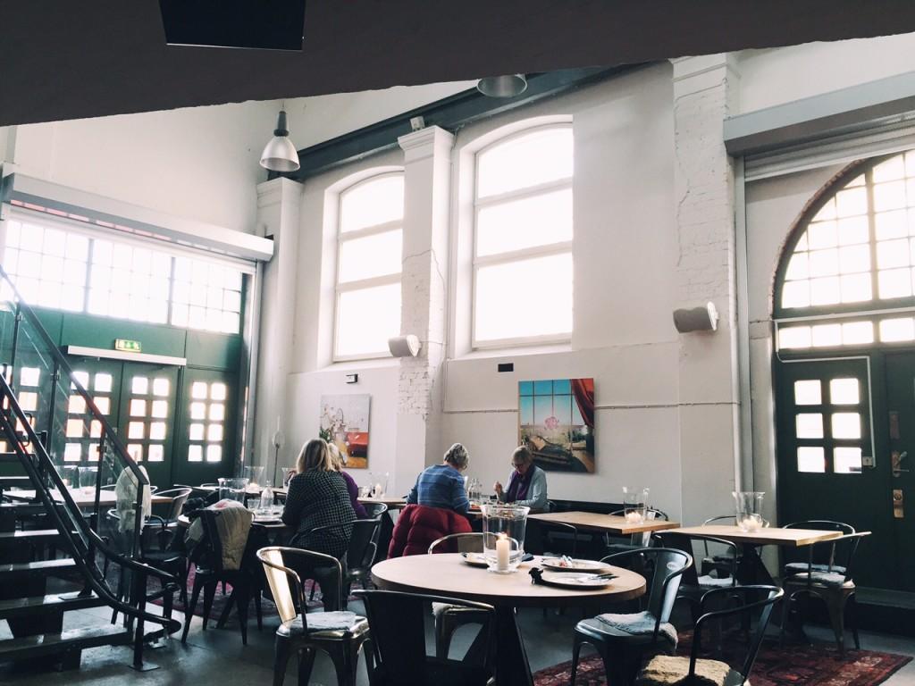 Restaurangmiljö, rustik, högt i tak och höga fönster.